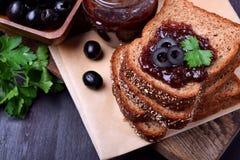 Oliwny marmoladowy w szklanym słoju i na plasterku chleb obrazy royalty free
