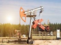 Olja för oljabrunn för tillverkning av och bensin och gas på bakgrunden av skogen, produktionen av bensin, pumpjack royaltyfria foton