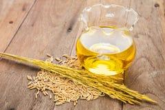 Olja för riskli i flaskexponeringsglas och unmilled ris på träbackgr Royaltyfria Bilder