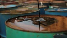 Olja häller ut på ett rostigt fat arkivfilmer