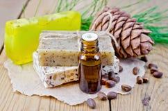 Olja och tvål som är olika med den cederträmuttrar och kotten på ett bräde Arkivfoto
