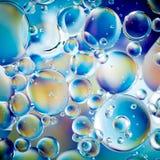 Oljabubblor på vattenyttersida arkivbilder