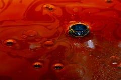 Oljafläck med ett hål i mitt Vätsketjockt arkivfoto