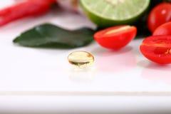 Oljapreventivpillerar för växt- medicin på grönsakbakgrund Royaltyfri Bild