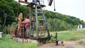 Oljapump i operation i skogområdet stock video