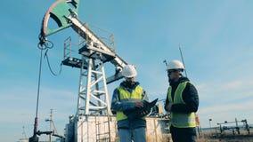 Oljapump med två specialister som har en diskussion framme av den lager videofilmer