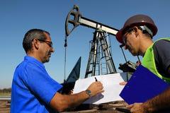 Oljateknikerer som diskuterar frågor på arbete Arkivbild