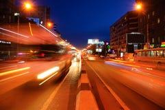 Oljde huvudvägljus i rörelse Mörk stad för afton bilar går vägen fotografering för bildbyråer