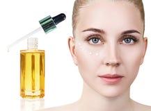 Olje- applicera för skönhetsmedel på framsida av den unga kvinnan Arkivbild