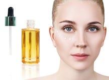 Olje- applicera för skönhetsmedel på framsida av den unga kvinnan Royaltyfria Foton
