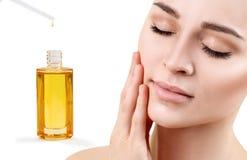 Olje- applicera för skönhetsmedel på framsida av den unga kvinnan Royaltyfri Fotografi