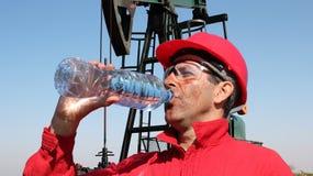 Olje- arbetare som tar avbrottet och dricker sötvatten Arkivbild