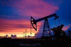 Olje- borrtorn på en bakgrund av den härliga solnedgången Royaltyfria Bilder