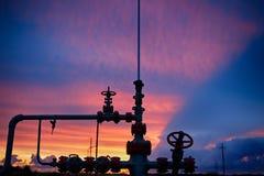 Olje- borrtorn på en bakgrund av den härliga solnedgången Royaltyfri Bild