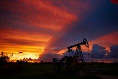 Olje- borrtorn på en bakgrund av den härliga solnedgången Arkivbild
