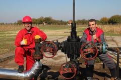 Olje- brunn och två olje- arbetare Arkivbild