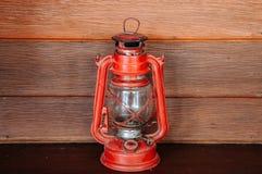 Olje- lampa för gammal fotogen för vinatge röd på träväggbakgrund Royaltyfri Bild