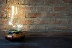 Olje- lampa på natten på en trätabell med gammal bakgrund för tegelstenvägg Royaltyfri Fotografi