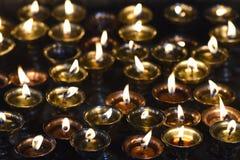 Olje- lampor för buddistisk bön med fastnade ljus på en svart bakgrund Arkivbilder