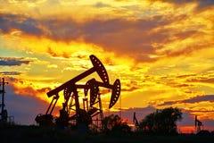 Olje- sugande maskinsolnedgångglöd royaltyfri bild