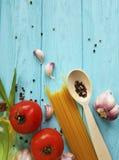 Olje- sund matmeny för spagetti, vitlöktomatsvartpeppar på en träblått Royaltyfri Fotografi