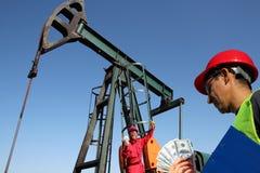Oljefältarbetare som rymmer pengar Royaltyfri Fotografi