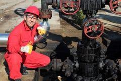 Oljefältarbetaren som visar det ok tecknet. Arkivbild