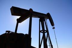 Oljefältpumpjack, rostigt och gammalt, silhouetted av solen royaltyfri bild