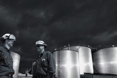 Oljeindustri, arbetare och mörka stormiga moln arkivbilder