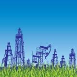 Oljeplattform och pump över blå bakgrund med gräs. Royaltyfri Fotografi