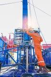 Oljeplattformarbetaren kontrollerar och inställningen - upp hjälpmedel för den bästa sidan för säkerhet första till brunnen för p Royaltyfri Foto
