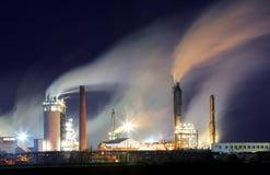 Oljeraffinaderi med dunsten - petrokemisk bransch på natten Arkivfoton