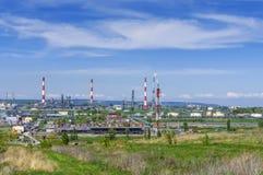 Oljeraffinaderi rör, brännande fackla, smällare, skrov, lagringsbehållare för oljaprodukter, mot bakgrunden av gräsplan arkivfoton