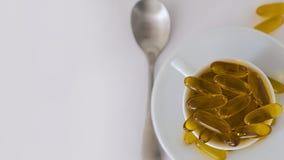 Oljiga diet-tilläggkapslar över spill av av en vitt keramiskt kopp och tefat, med en silvertesked på vänstersidahandsidan och whe Royaltyfri Bild
