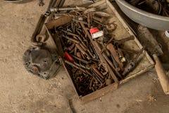 Oljiga hjälpmedel med den stora skiftnyckelskruvnyckeln - gamla Rusty Toolbox på det jord - fetthaltiga bitar och smutsig murslev royaltyfri bild