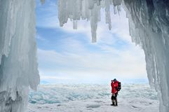 Olkhon island, Baikal, Russia, 12, March, 2017.Tourist photographing ice hummocks on lake Baikal in the background of the ice grot. Olkhon island, Baikal Stock Images