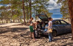 Tourists gather beside the car. Royalty Free Stock Image