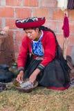 Ollantaytambo, Perù - circa giugno 2015: La donna in vestiti peruviani tradizionali usa la tintura naturale per alpaga e la lana  Immagine Stock Libera da Diritti