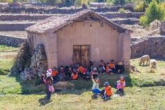 Ollantaytambo, Perú - circa junio de 2015: Los niños en ropa peruana tradicional están esperando un autobús del schoold cerca de  foto de archivo libre de regalías