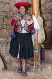 Ollantaytambo, Peru - circa Juni 2015: De vrouw in traditionele Peruviaanse kleren maakt garen van Alpaca en Lamawol dichtbij Cus Royalty-vrije Stock Fotografie