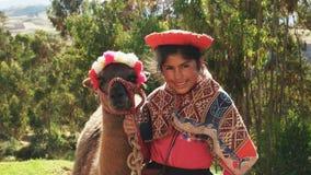 OLLANTAYTAMBO, PERU-MAY, 17, 2016: a peruvian girl poses with a llama near ollantaytambo