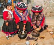 Ollantaytambo, Peru - około Czerwiec 2015: Kobiety w tradycyjnych Peruwiańskich ubraniach używają naturalnych barwidła dla alpagi fotografia stock