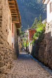 Ollantaytambo, Urubamba/Peru - circa Juni 2015: Oude smalle straat en baksteengebouwen in de stad van Ollantaytambo Inca stock foto