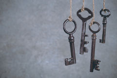 Olld keys hanging on cool. Four old keys hanging on light cool abstract background with copy space. Security concept Stock Photography