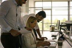 olleague in bureau die computer met behulp van het controleren documenteert B Royalty-vrije Stock Foto's