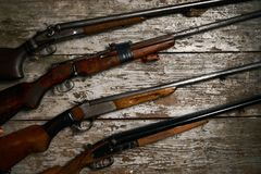 Ollection of hunting rifles. Rifles, shotguns on wooden table background, Hunting guns close-up Royalty Free Stock Images