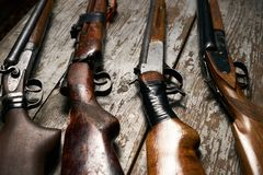 Ollection of hunting rifles. Rifles, shotguns on wooden table background, Hunting guns close-up Royalty Free Stock Image