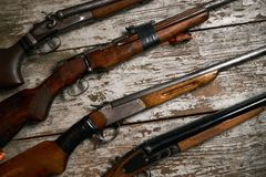 Ollection of hunting rifles. Rifles, shotguns on wooden table background, Hunting guns close-up Royalty Free Stock Photo