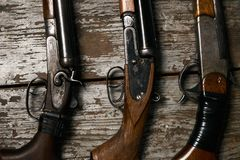 Ollection of hunting rifles. Rifles, shotguns on wooden table background, Hunting guns close-up Royalty Free Stock Photography