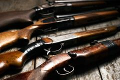 Ollection of hunting rifles. Rifles, shotguns on wooden table background, Hunting guns close-up Stock Photos